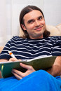 Happy man writing diary on sofa Royalty Free Stock Image