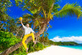 Happy man in yellow trousers and white shirt sitting on a palm t Royalty Free Stock Photo