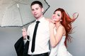 Happy married couple bride groom on gray background wedding day portrait of blue eyed with her red hair blowing in the wind and Stock Photos