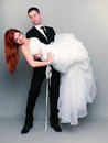 Happy married couple bride groom on gray background wedding day portrait of holding red haired up in his hands full length studio Royalty Free Stock Images