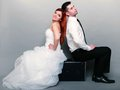 Happy married couple bride groom on gray background wedding day portrait of red haired and in full length sitting old suitcase Stock Photography