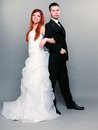 Happy married couple bride groom on gray background wedding day portrait of red haired and in full length studio shot Royalty Free Stock Photography