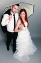 Happy married couple bride groom on gray background wedding day portrait of red haired and in full length with umbrella studio Stock Images