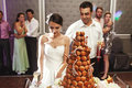 Happy married couple eating delicious chocolate wedding cake at Royalty Free Stock Photo
