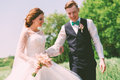 Happy married couple walking on field at sunny day Royalty Free Stock Photo