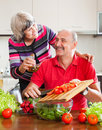 Happy married mature couple cooking together in kitchen at home Stock Images