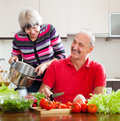 Happy married mature couple cooking with tomatoes in kitchen at home Royalty Free Stock Images