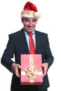Happy mature business man with santa hat is giving you a presen present on white background Stock Photography