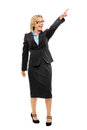 Happy mature business woman pointing isolated on white backgroun full length Stock Photography