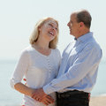 Happy mature couple against sea portrait of in background Stock Photography