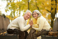 Happy mature couple in autumn day sitting on bench Stock Photos