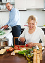Happy mature couple cooking healthy food at home kitchen Royalty Free Stock Photography