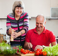 Happy mature couple cooking veggy lunch in home kitchen Stock Image