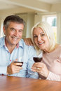 Happy mature couple drinking red wine at home in the kitchen Stock Image