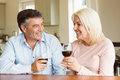 Happy mature couple drinking red wine at home in the kitchen Royalty Free Stock Photo