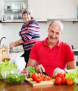 Happy mature couple with fresh vegetables and greens in home kitchen Stock Photos