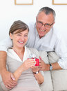 Happy mature couple getting gift at home Stock Photography