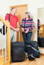 Happy mature couple going on holiday with luggage near door Stock Photography