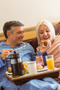 Happy mature couple having breakfast in bed at home bedroom Royalty Free Stock Photo