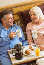 Happy mature couple having breakfast in bed at home bedroom Royalty Free Stock Photography