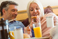 Happy mature couple having breakfast in bed at home bedroom Stock Photos