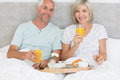Happy mature couple having breakfast in bed portrait of at home Stock Photos