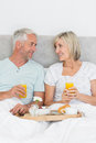 Happy mature couple having breakfast in bed portrait of at home Royalty Free Stock Photo