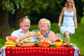 Happy mature couple having picnic outdoors Stock Photo