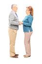 Happy mature couple holding hands and looking each other full length portrait of a isolated on white background Royalty Free Stock Images