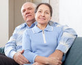 Happy mature couple in home on sofa Stock Images