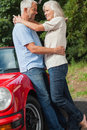 Happy mature couple hugging against their red cabriolet on a sunny day Royalty Free Stock Photos