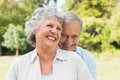Happy mature couple laughing in the park on sunny day Stock Photo