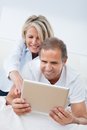 Happy mature couple looking at digital tablet man using woman from behind Stock Photography