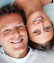 Happy mature couple lying down head close together Stock Image