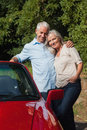 Happy mature couple posing against their red cabriolet Royalty Free Stock Photos