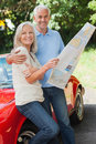 Happy mature couple reading map together by their cabriolet Stock Image