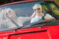 Happy mature couple in red cabriolet going for a ride on sunny day Stock Image