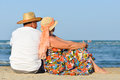 Happy mature couple sitting at seashore on sandy beach back to back sea summer outdoors background Stock Photography