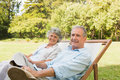 Happy mature couple sitting on sun loungers in park looking at camera Royalty Free Stock Photos