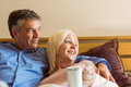 Happy mature couple smiling on bed at home in bedroom Royalty Free Stock Images