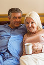 Happy mature couple smiling at camera on bed home in bedroom Royalty Free Stock Photo