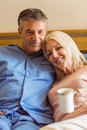Happy mature couple smiling at camera on bed home in bedroom Royalty Free Stock Image
