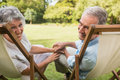Happy mature couple smiling at camera and looking in park on deck chairs Stock Image