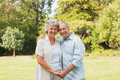 Happy mature couple smiling and looking at camera in the park Royalty Free Stock Images