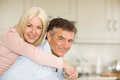 Happy mature couple smiling together at home in the kitchen Stock Photo