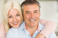 Happy mature couple smiling together at home in the kitchen Stock Image