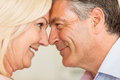Happy mature couple smiling together at home in the kitchen Stock Photos
