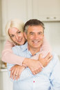 Happy mature couple smiling together at home in the kitchen Stock Images