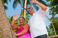 Happy mature couple with snorkeling gear waving Royalty Free Stock Photos