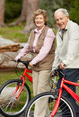 Happy mature couple standing with bicycle Stock Photography